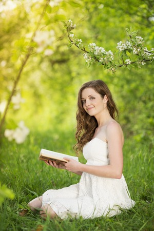 Beutiful young woman reading book in green park photo