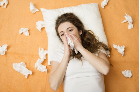 Sick woman lying in bed with cold and flu  She is blowing nose