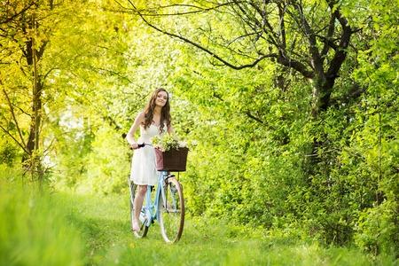Pretty young woman riding retro bike in green park photo