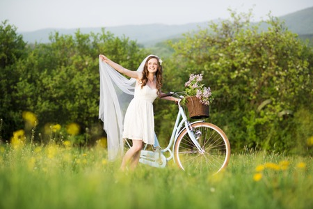 Pretty young bride riding retro bike in green meadow photo