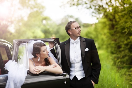 Beautiful happy young bride and groom posing by the retro car  Outdoor wedding portrait  photo