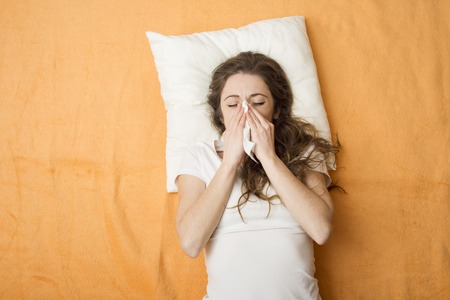 Sick woman lying in bed with cold and flu  She is blowing nose Stock Photo - 26864005