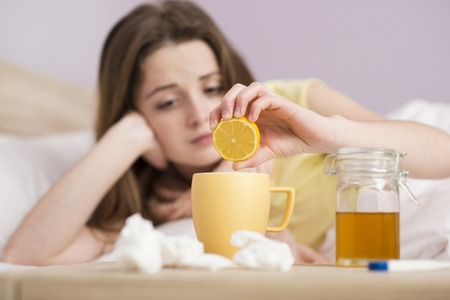 Sick woman lying in bed with high fever  She has cold and flu  She is drinking tea with honey and lemon