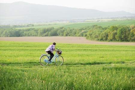 Young man riding vintage bike on the green meadow photo