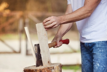 Detail of young man chopping wood in his backyard Stock Photo