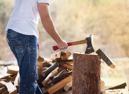 若い男が彼の裏庭で薪割りの詳細 写真素材
