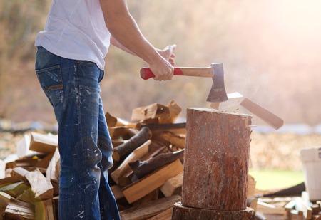 Detail van jonge man hakken hout in zijn achtertuin Stockfoto