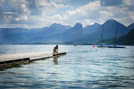 Young woman sitting on the pier by the lake photo