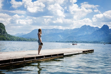 Young woman standing on the pier by the lake photo