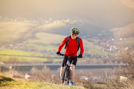 Men exercise: Mountain biker is ridding bike outdoor