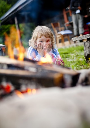 campfires: Cute girl playing with fire Stock Photo