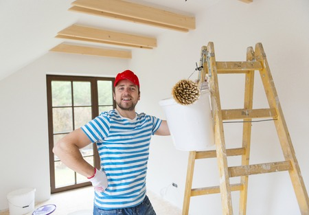 Happy smiling man is painting his new home  photo