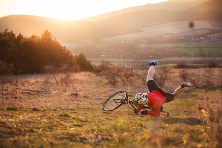hombre cayendo: Hombre Ciclista que monta en bicicleta de montaña en la pista al aire libre en una pradera soleada Foto de archivo