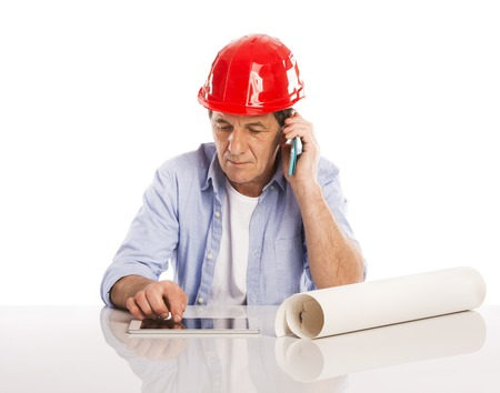 Portrait Of Happy Senior Engineer Making Phone Call And Looking To Plans Isolated Over White Background photo