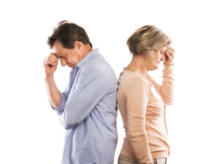 couple arguing: Studio foto de pareja de ancianos enojados que tienen un argumento, aislados en fondo blanco El matrimonio en crisis