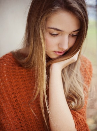 Outdoor portrait of beautiful young sad girl thinking about something
