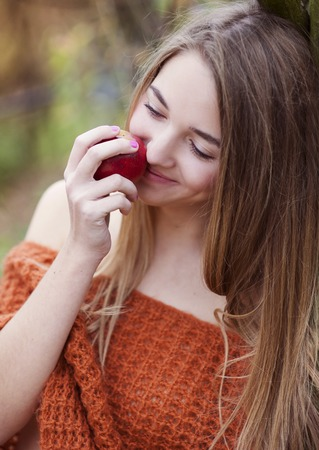 Outdoor portrait of beautiful girl holding an apple photo