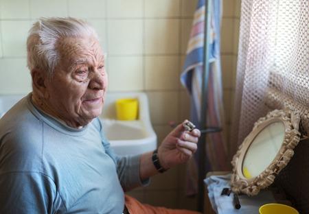 Senior man shaving his beard in bathroom in front of the mirror Stock Photo