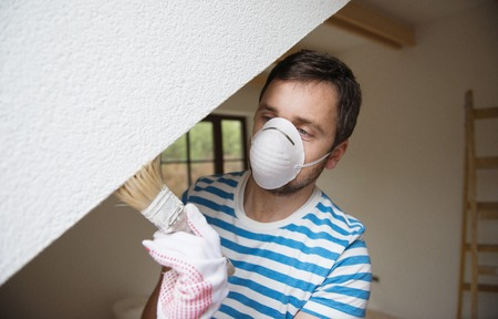 Happy smiling man painting the walls of new home with paintbrush while wearing respiratory safety equipment photo