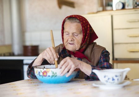 Very old woman preparing food in her old country style kitchen photo