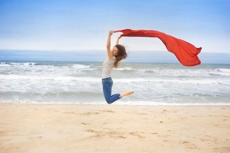 Sport active woman jumping at the beach with red scarf photo