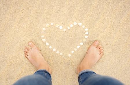 uñas pintadas: Pies femeninos primer plano de mujer de pie en la playa de arena junto al corazón de shell Foto de archivo