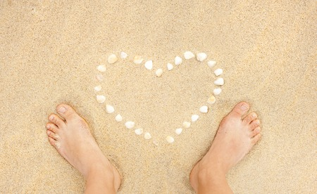 feet in sand: Female feet closeup of woman standing at the sandy beach next to the shell heart