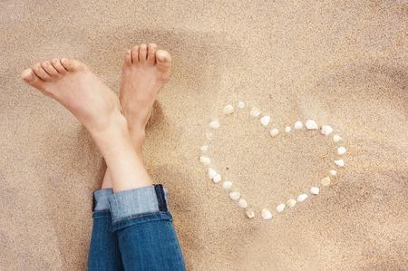 u�as pintadas: Pies femeninos primer plano de mujer de pie en la playa de arena junto al coraz�n de shell Foto de archivo