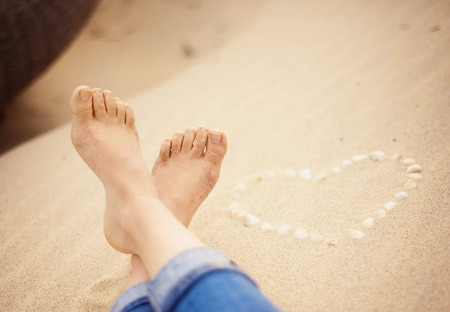 painted toenails: Female feet closeup of woman standing at the sandy beach next to the shell heart