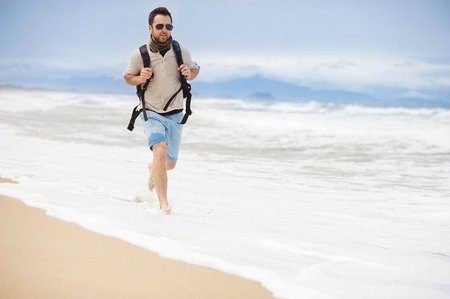 Handsome young Caucasian man walking alone with backpack on the beach photo