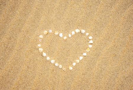 Small seashells in the shape of a heart on a sandy beach photo