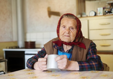 Very old woman in head scarf is drinking tea in her old country style kitchen photo