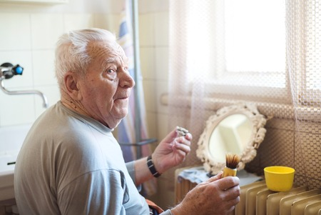 beautycare: Senior man shaving his beard in bathroom in front of the mirror Stock Photo
