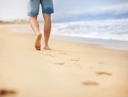 Detail van mannelijke voeten lopen op het strand