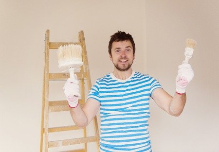 Happy smiling man painting the walls of new home with paintbrush photo