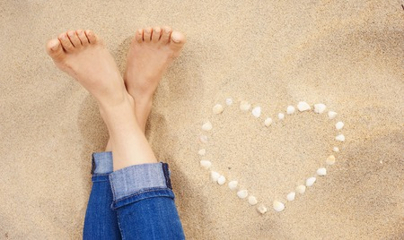 Female feet closeup of woman standing at the sandy beach next to the shell heart photo
