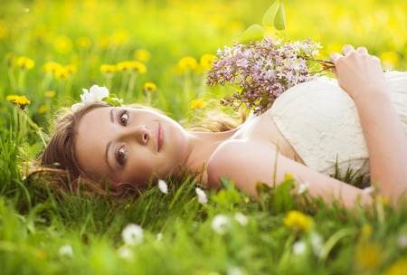Beautiful girl is relaxing lying on the grass in the garden photo