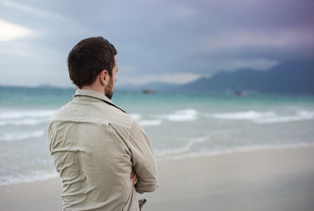 Handsome young Caucasian man walking alone on the beach Stock Photo