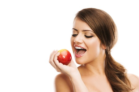 Smiling beautiful woman holding red apple while isolated on white photo