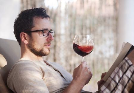 personas leyendo: Hombre guapo joven relajándose, libro de lectura y beber vino tinto Foto de archivo