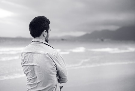 walking alone: Black and white portrait of handsome young Caucasian man walking alone on the beach Stock Photo