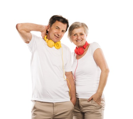 Senior couple listening to music with headphones, isolated on white photo
