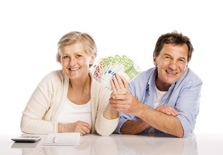 Senior couple counting money at the table, isolated on white background photo