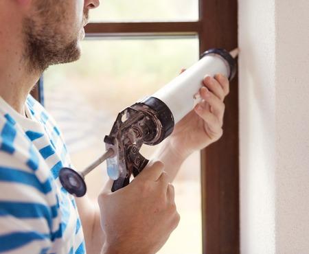 Man applying silicone sealant with caulking gun photo