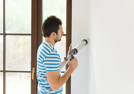 Man applying silicone sealant with caulking gun photo