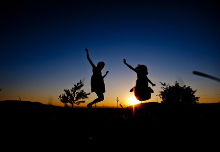 Silhouette of two jumping girls  photo