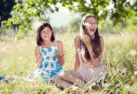 Two sisters laughing together at the meadow  photo