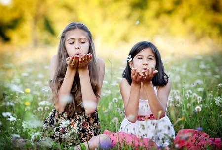 Two sisters laughing and playing in green sunny park photo