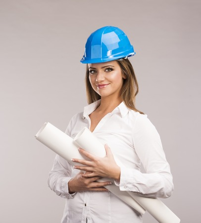 Portrait of Young woman architect with blue hard hat and paper plans photo