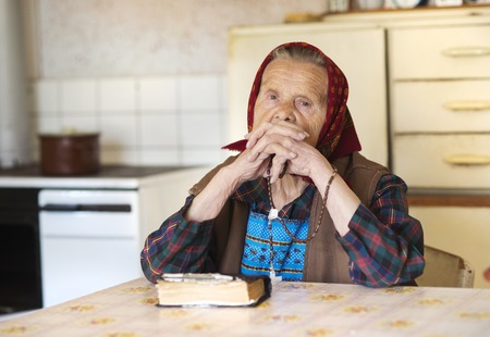 Very old woman wearing head scarf is praying in her country style kitchen photo
